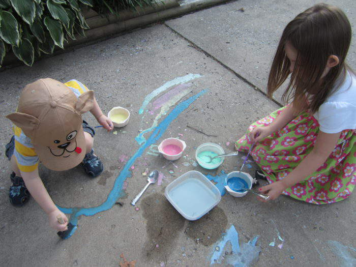 two young kids painting the sidewalk with sidewalk chalk paint