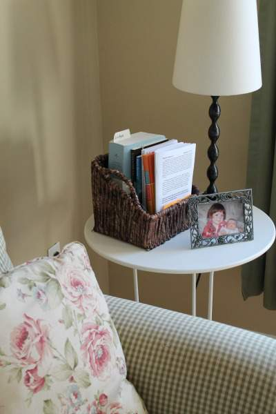 side table in family room with a book basket