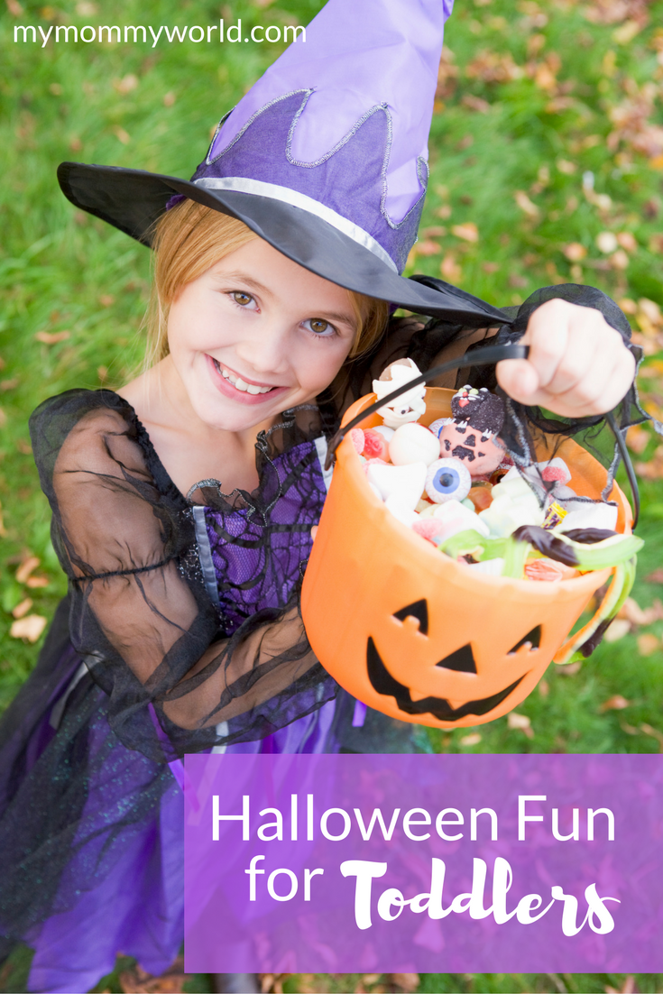 young girl dressed in a witch costume holding a jack o'lantern