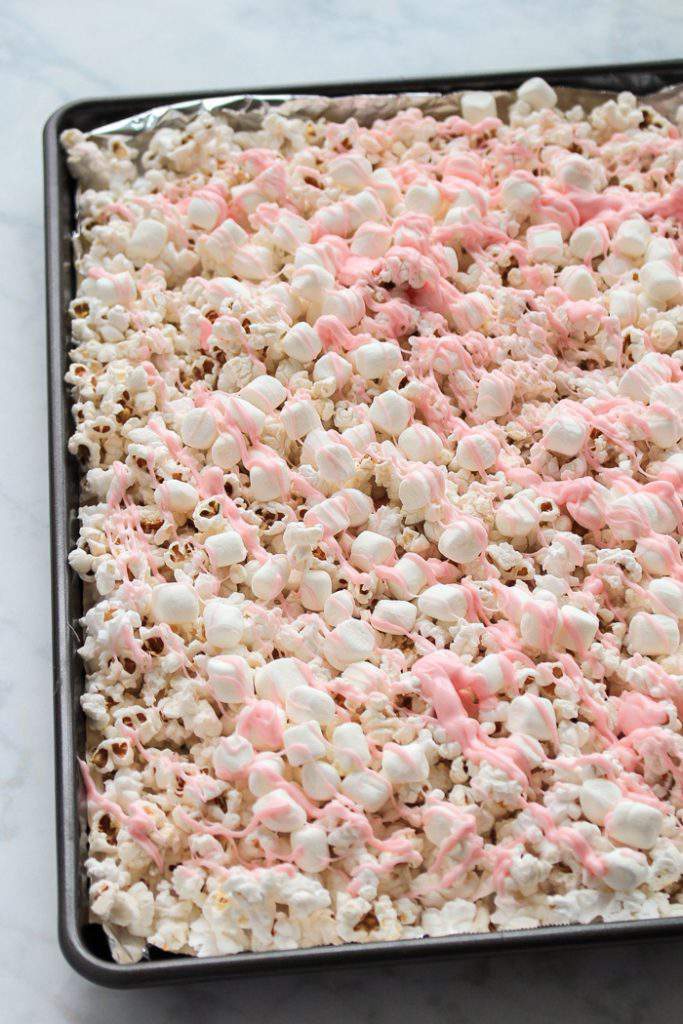 melted pink candy drizzled over popcorn and marshmallows