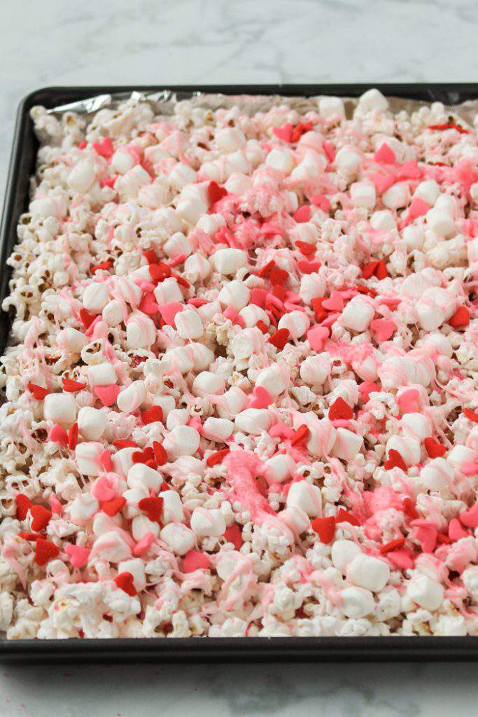 valentine's popcorn with pink candy drizzle and heart candies