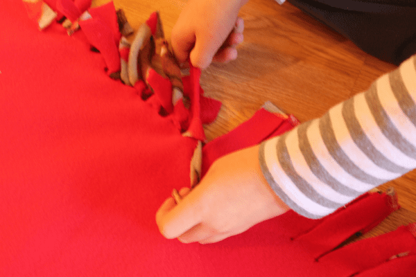 child tying the edges of the blanket