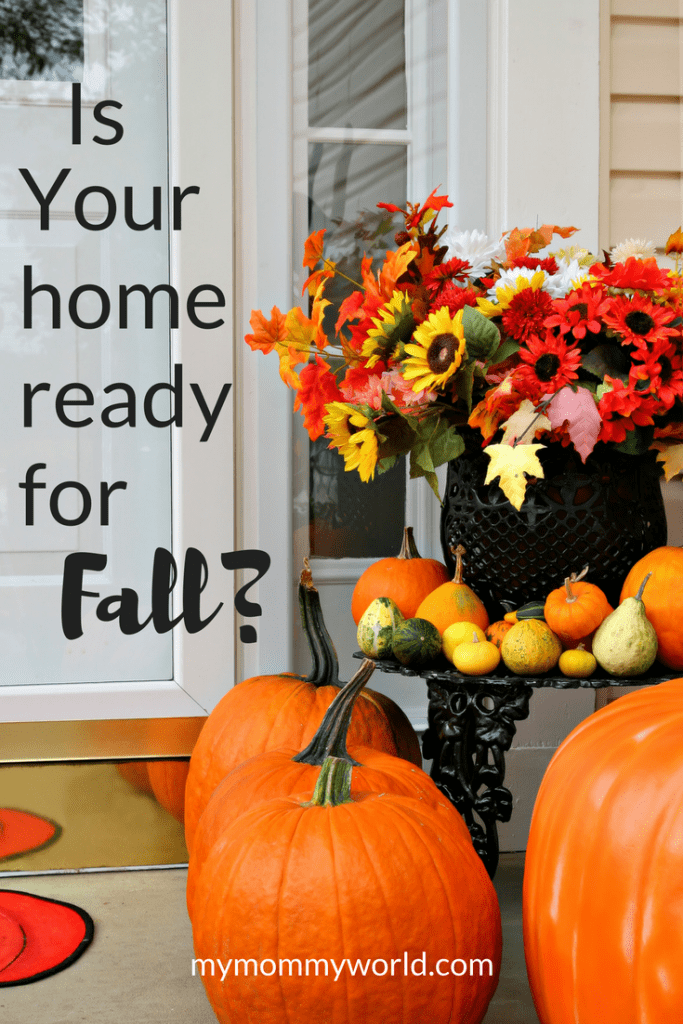 fall-themed flower and pumpkin arrangement sitting on the front porch of a home