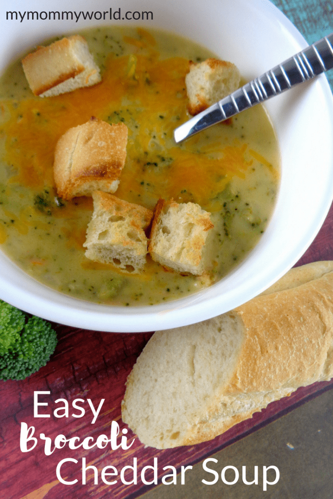 Bowl of broccoli cheddar soup with piece of bread.