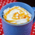 mug of caramel latte with whipped cream and caramel swirl on top