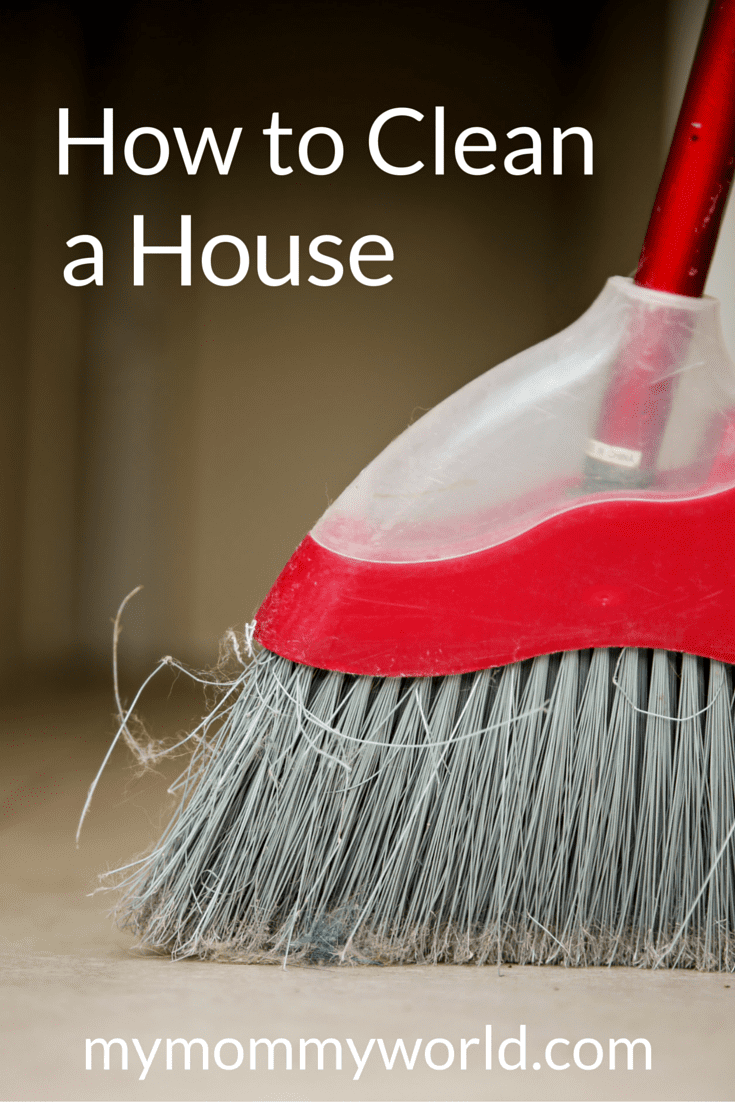 red handled broom sweeping a floor
