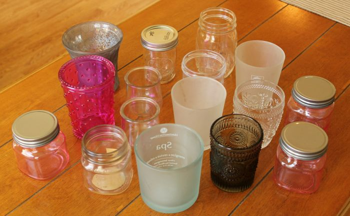 a collection of glass candle containers