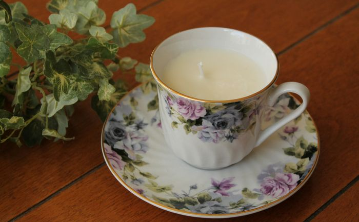tea cup candle and ivy on a table