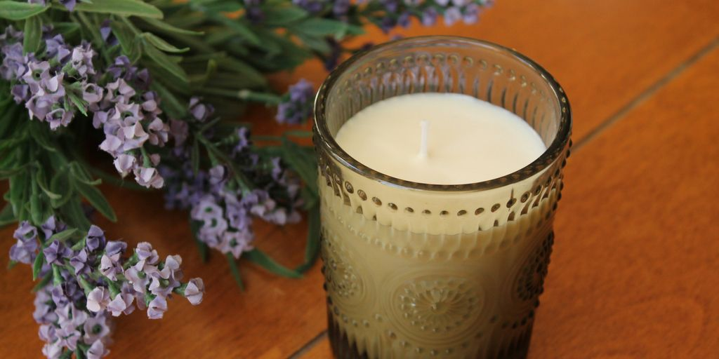 homemade candle and lavender flowers on a table
