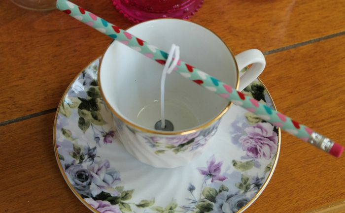 a candle wick wrapped around a pencil sitting across a tea cup