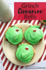 plate of cinnamon rolls decorated like the grinch with green icing and a red candy heart