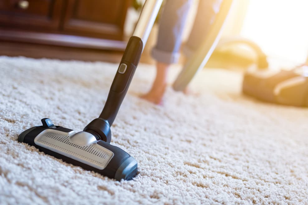 woman vacuuming the carpet in her home.